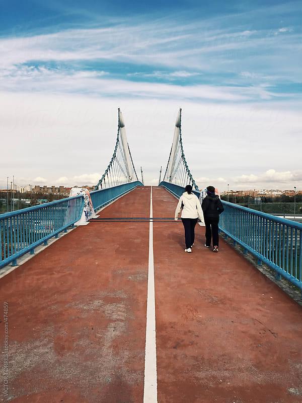 People Walking Through a Pedestrian Footpath Along a Big Bridge by VICTOR TORRES for Stocksy United