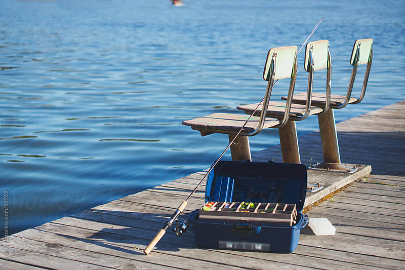 A fishing pole and tackle box sit on a dock next to old fishing chairs by Tana Teel for Stocksy United