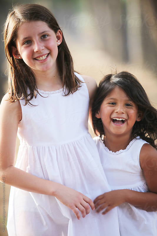 hispanic and caucasian girl in white dresses hugging and laughing outdoors by Dina Giangregorio for Stocksy United