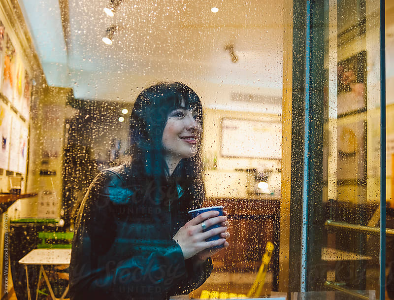 Woman relaxing in a cafe during rainy day by GIC for Stocksy United