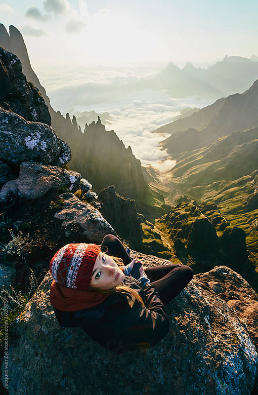 A female hiker sitting at the summit of a beautiful mountainous valley at sunrise. by Jacques van Zyl for Stocksy United