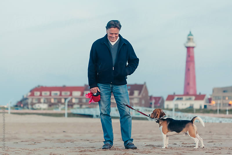 Older man with a beagle dog on a leash standing on the beach by Cindy Prins for Stocksy United