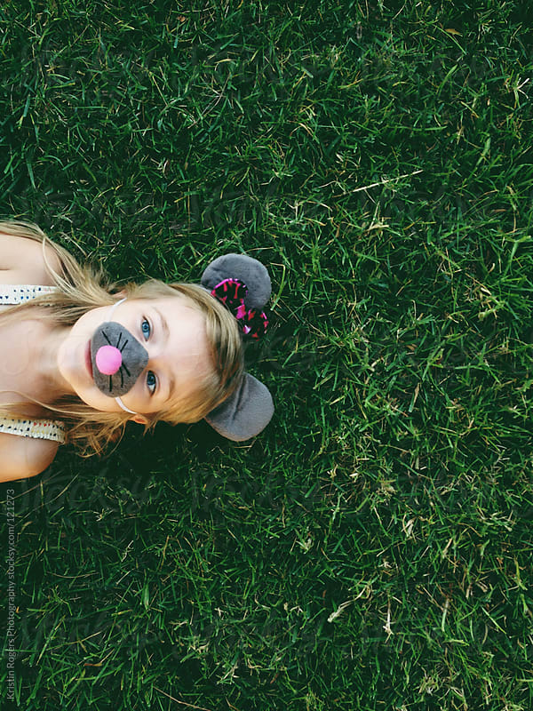 young girl with mouse ears and nose on laying in grass by Kristin Rogers Photography for Stocksy United