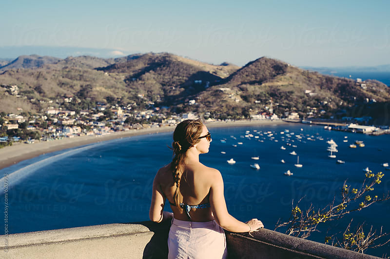 Brunette looking out onto the Bay by Oscar Lopez for Stocksy United