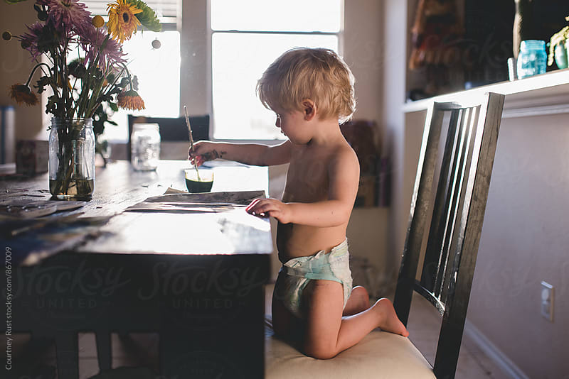 Toddler paints in a diaper by Courtney Rust for Stocksy United