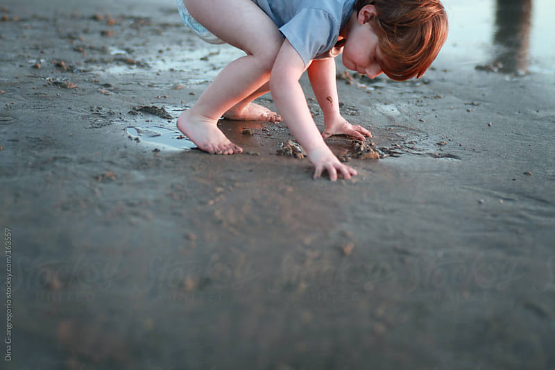 Toddler boy playing in sand at the beach by Dina Giangregorio for Stocksy United