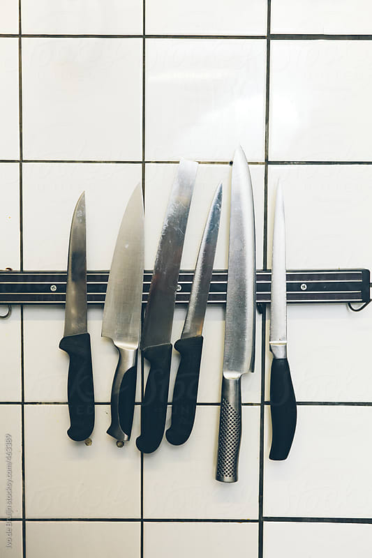 Chef's knives hanging on the wall, being held by a magnet by Ivo de Bruijn for Stocksy United