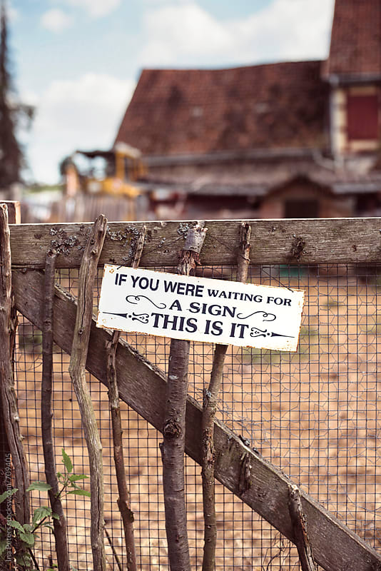 Objects: If you were waiting for a sign, this is it, at a fence by Ina Peters for Stocksy United