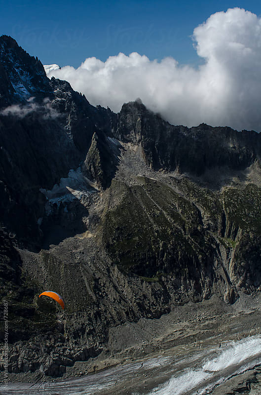 Paragliding over glacier and mountains in the alps by Neil Warburton for Stocksy United