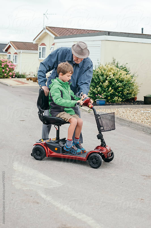 Young boy learning to drive scooter with Grandad\'s help