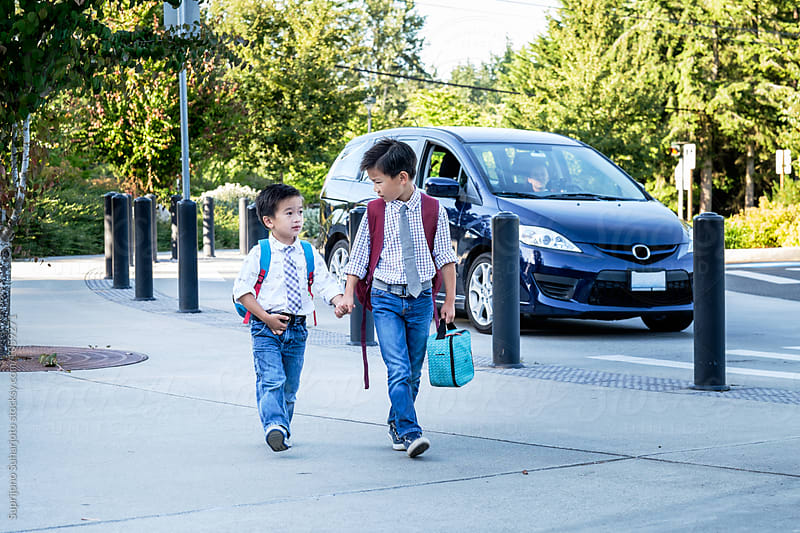 Back to school: Asian kids walking in school after dropped off by their mother by Suprijono Suharjoto for Stocksy United