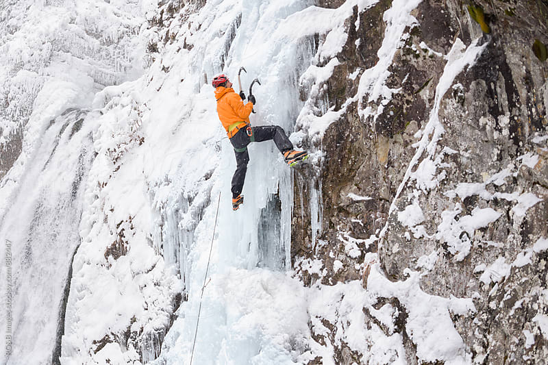 Male alpinist climbing an ice waterfall by RG&B Images for Stocksy United