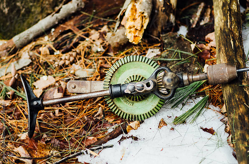 old green hand drill on snowy forest ground by Deirdre Malfatto for Stocksy United