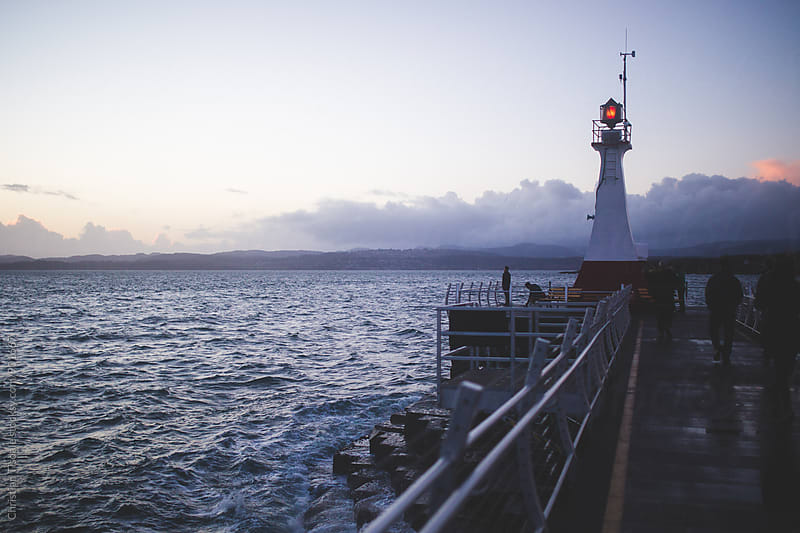 Lighthouse overlooking the pacific at sunset by Christian Tisdale for Stocksy United