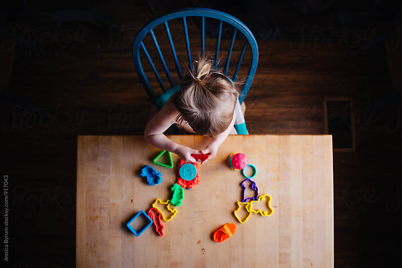 Toddler playing with colorful dough by Jessica Byrum for Stocksy United