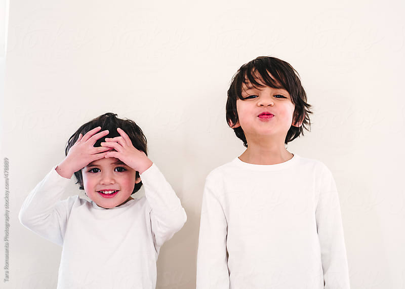 little boys in white on white, smiling and laughing by Tara Romasanta for Stocksy United