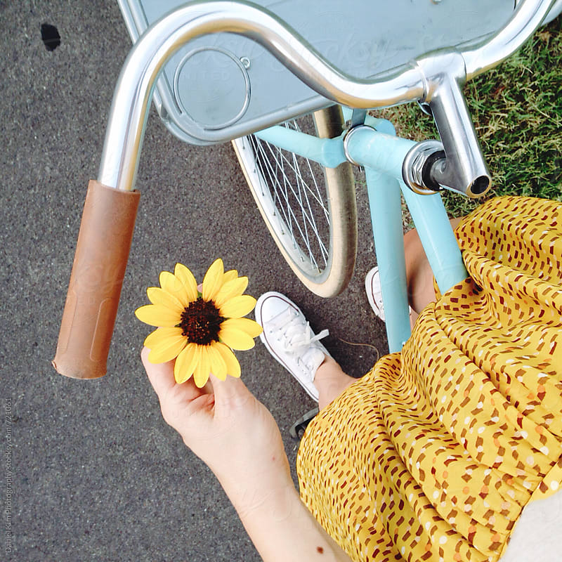 Woman holding flower on bike by Daniel Kim Photography for Stocksy United