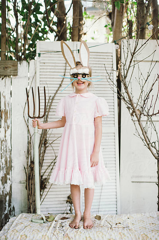 Little girl with homemade bunny mask holding pitch fork by Kristin Rogers Photography for Stocksy United