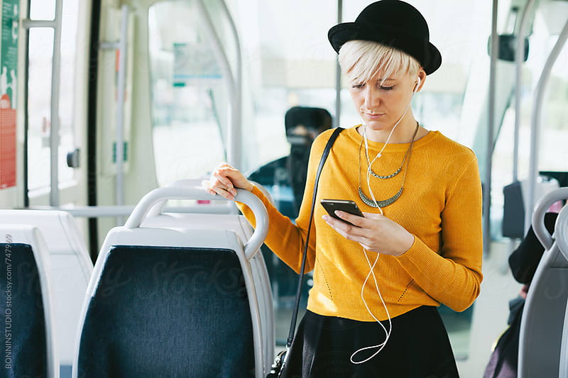 Blonde chic woman using her smartphone standing in the train. by BONNINSTUDIO for Stocksy United