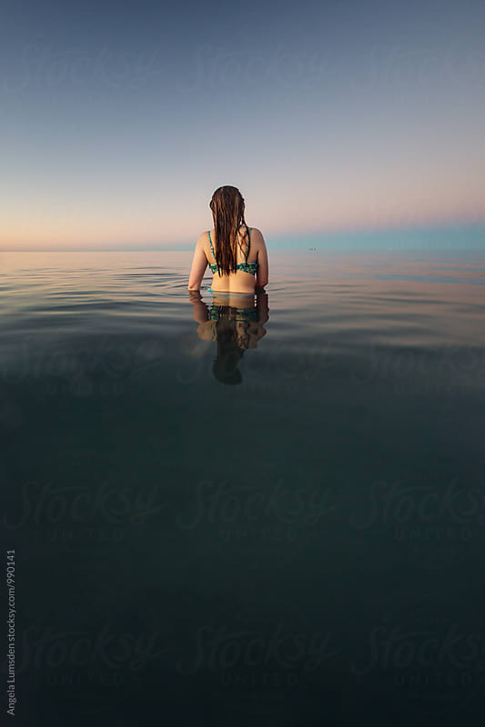 Teenage girl viewed from behind standing in waist deep ocean water after sunset by Angela Lumsden for Stocksy United