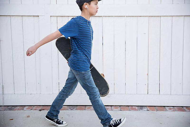 Boy holding his skateboard and walking by Curtis Kim for Stocksy United