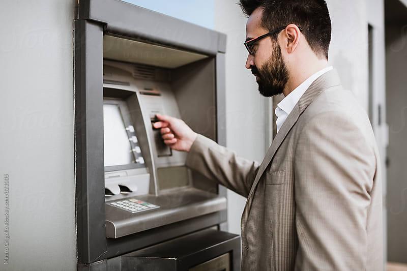 Businessman using an ATM by Mauro Grigollo for Stocksy United