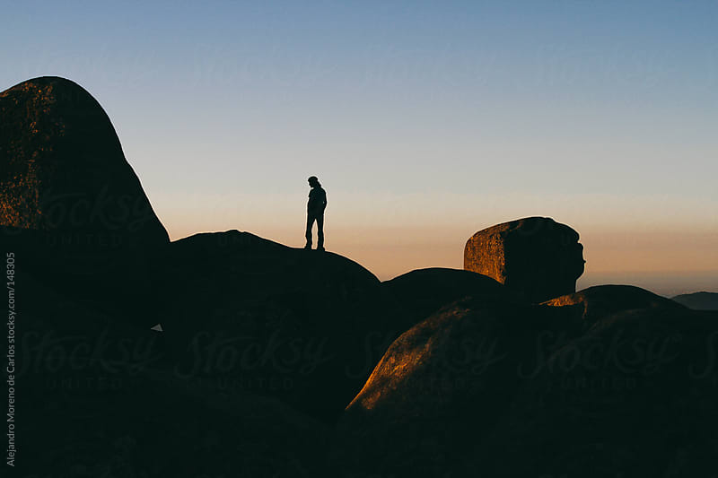 Man silhouette on top of a boulder at sunrise by Alejandro Moreno de Carlos for Stocksy United
