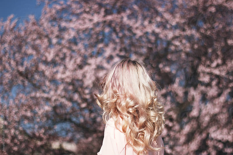 Young woman looking at cherry blossom tree. by Jovana Rikalo for Stocksy United