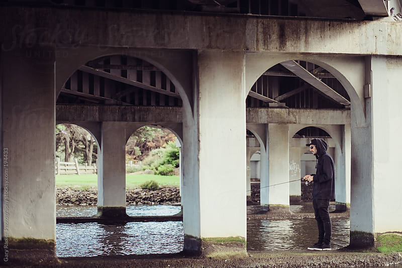 Young Man Fishing under a Bridge by Gary Radler Photography for Stocksy United