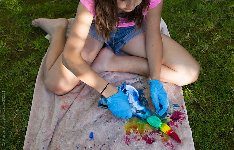 Young girl tie-dying a shirt on the grass at home  by Carolyn Lagattuta for Stocksy United