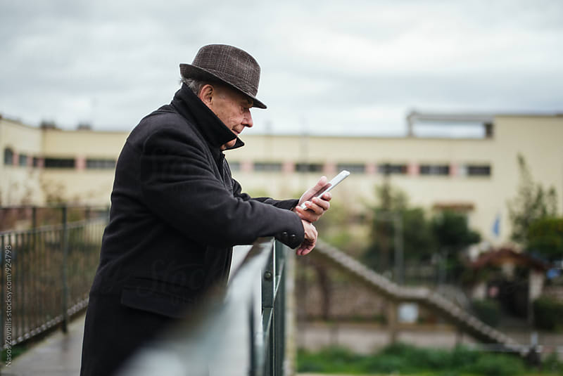 Portrait of a senior man using smartphone outdoor by Nasos Zovoilis for Stocksy United