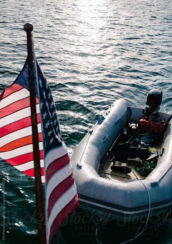 Small inflatable sailing dinghy boat on stern of boat with flag by Matthew Spaulding for Stocksy United