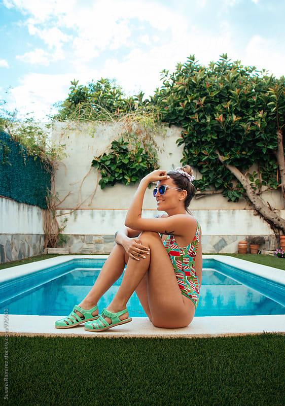 Smiling beautiful woman with a swimsuit, at the edge of the pool by Susana Ramírez for Stocksy United