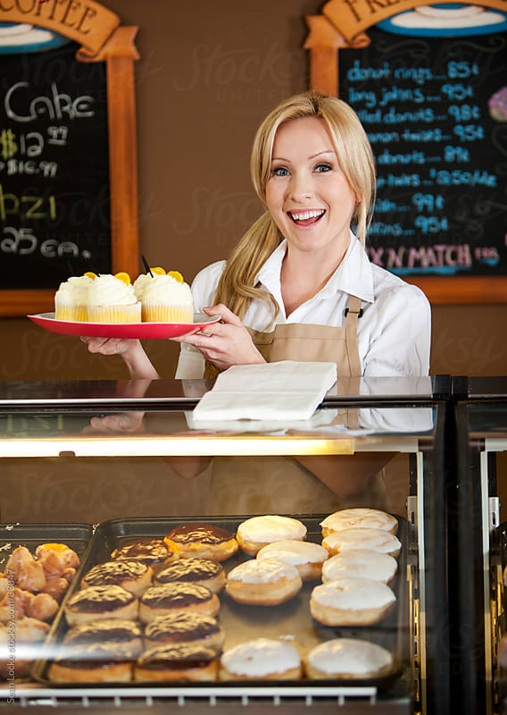 Bakery: Cheerful Bakery Owner with Tray of Cupcakes by Sean Locke for Stocksy United