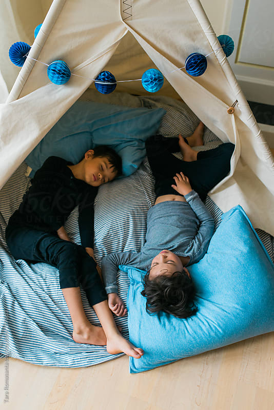 young children asleep in a teepee fort in a living room by Tara Romasanta for Stocksy United
