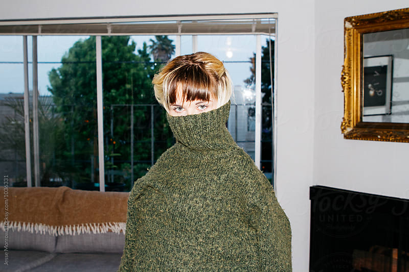 portrait of young female wearing fashionable high collar sweatshirt only showing eyes in apartment indoors by Jesse Morrow for Stocksy United