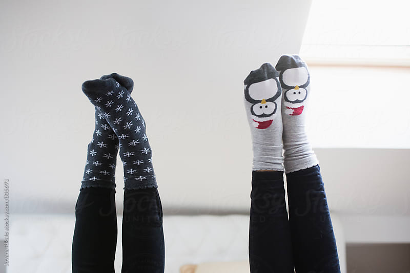Two female friends wearing Christmas socks by Jovana Rikalo for Stocksy United