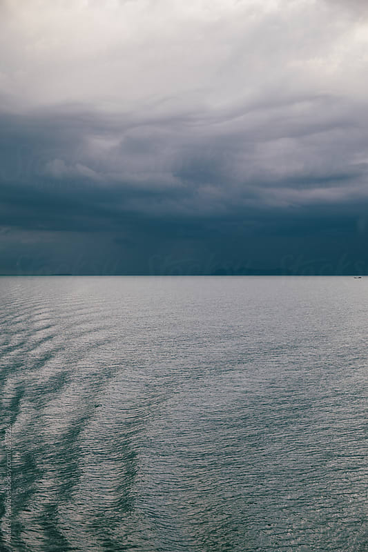 Beautiful photo of stormy clouds above the calm sea by Andrey Pavlov for Stocksy United