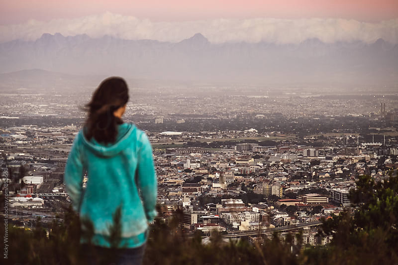 Woman overlooking a city view at dusk by Micky Wiswedel for Stocksy United