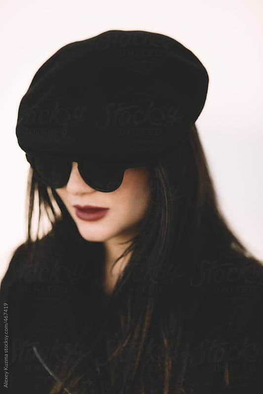 closeup of young woman with black cap and round sunglasses by Alexey Kuzma for Stocksy United