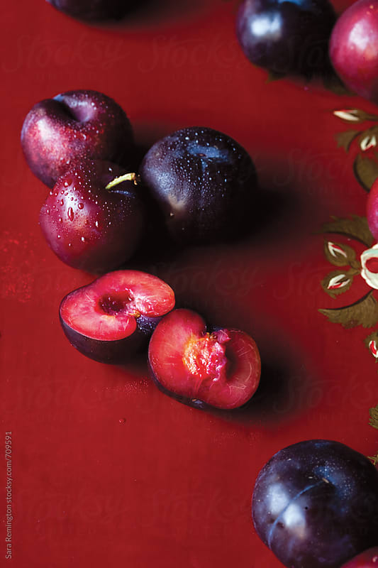 Organic Plums on Red Surface by Sara Remington for Stocksy United