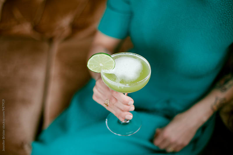 Woman holding a fancy green cocktail by Jen Brister for Stocksy United