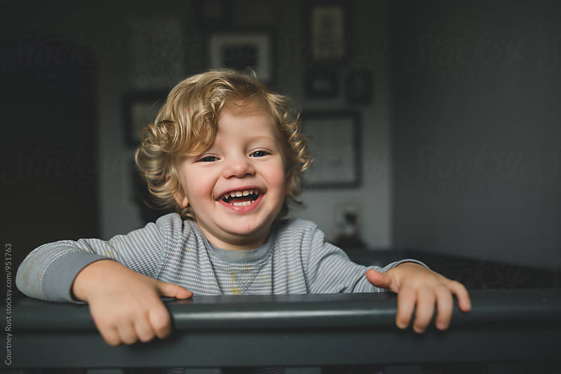Little Boy smiling over crib by Courtney Rust for Stocksy United