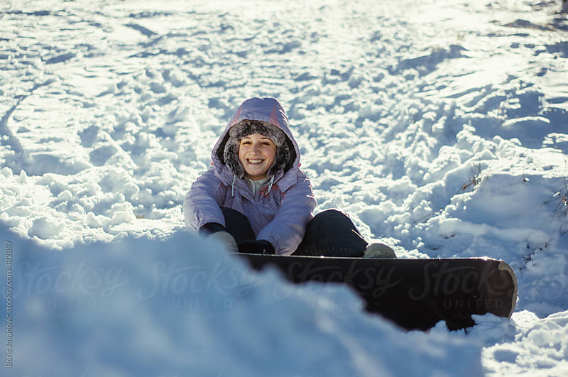 Snowboarder shifting her board by Boris Jovanovic for Stocksy United