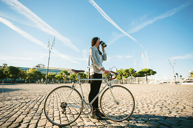 Businesswoman standing with her vintage bicycle and drinking a coffee outside. by BONNINSTUDIO for Stocksy United