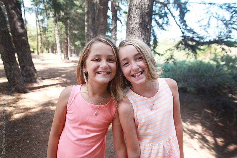 Portrait of happy twin sisters in a forest by Dina Giangregorio for Stocksy United