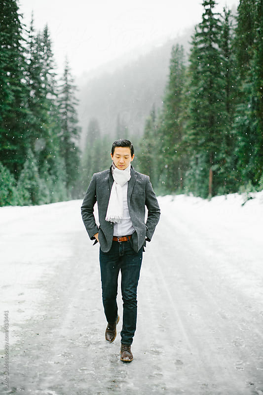 Young man walking in the snow by Luke Liable for Stocksy United