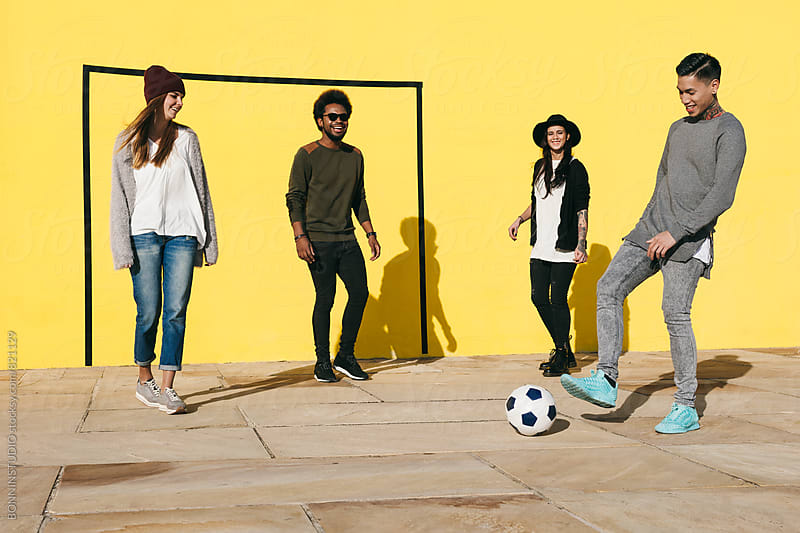 Group of friends having fun playing football in front of a yellow wall. by BONNINSTUDIO for Stocksy United