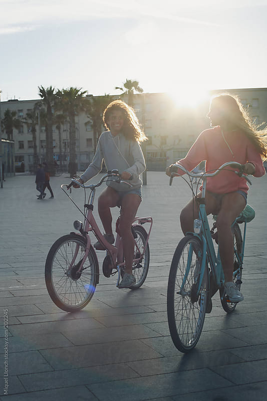 Two young girls riding their bicycles in Barcelona city at sunset by Miquel Llonch for Stocksy United