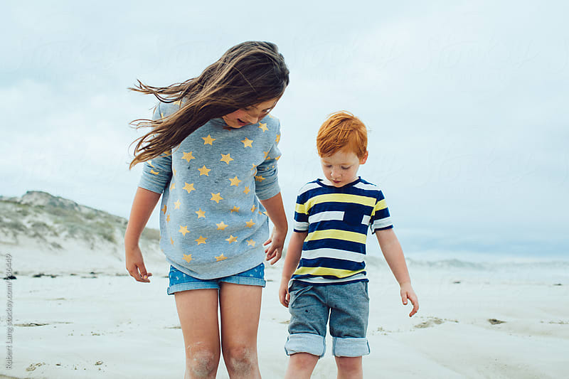 Brother and sister at the beach together by Robert Lang for Stocksy United